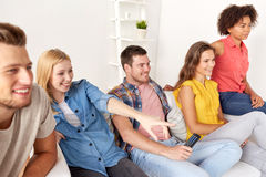 Happy friends with remote watching tv at home Stock Photo