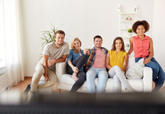 Happy friends with remote watching tv at home Royalty Free Stock Images