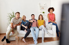 Happy friends with remote watching tv at home Stock Photography