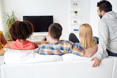 Happy friends with remote watching tv at home. Friendship, people and entertainment concept - happy friends with remote watching tv at home Royalty Free Stock Photo
