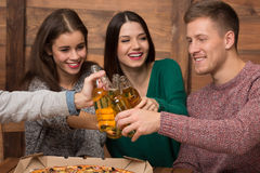 Happy friends resting with alcohol drinks in pizzeria Stock Photo