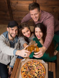 Happy friends resting with alcohol drinks in pizzeria Stock Images