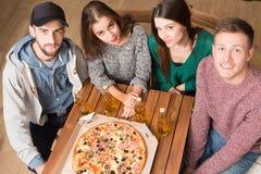 Happy friends resting in pizzeria Stock Photos