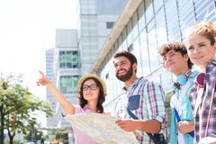 Happy friends with road map with woman pointing away in city Stock Photo