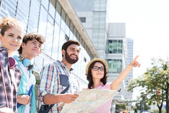 Happy friends with road map with woman pointing away in city Royalty Free Stock Images