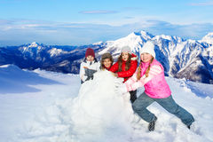Happy friends rolling big snowball Royalty Free Stock Photo