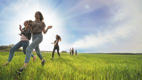 Happy friends run against the backdrop of a beautiful sky and sun. Happy friends run against the backdrop of a beautiful sky and sun stock video footage