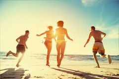 Happy friends run sunset beach holidays stock photo