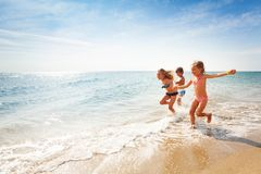 Happy friends running along edge of sea in summer Stock Photos