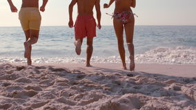 Happy friends running into the sea. In slow motion stock video