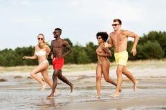 Happy friends running on summer beach stock photo