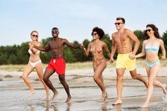 Happy friends running on summer beach stock photos