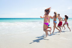 Happy friends running in the water together Stock Photography