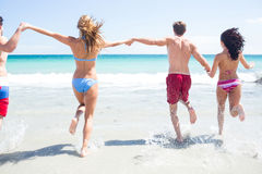 Happy friends running in the water together. At the beach Royalty Free Stock Images