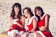 Happy friends in santa hats on the beach. Christmas vacation Royalty Free Stock Photos