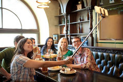 Happy friends with selfie stick at bar or pub. People, leisure, friendship and technology concept - happy friends taking picture by smartphone selfie stick Royalty Free Stock Image