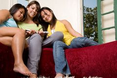 Happy friends sharing a book #2 - People Series. 3 females with smiles reading a book together on a red couch with the window open Royalty Free Stock Photo
