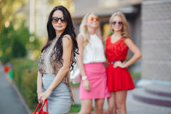 Happy friends with shopping bags ready to shopping. Three happy girlfriends, two blondes and the brunette, in sun glasses, are dressed in easy summer dresses Stock Photography