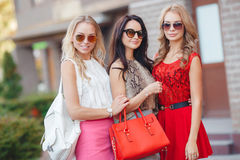 Happy friends with shopping bags ready to shopping. Three happy girlfriends, two blondes and the brunette, in sun glasses, are dressed in easy summer dresses Royalty Free Stock Photography