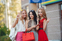 Happy friends with shopping bags ready to shopping. Three happy girlfriends, two blondes and the brunette, in sun glasses, are dressed in easy summer dresses Stock Image
