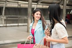 Happy friends shopping in city. Happy friends look at each other at outdoor department store. Two beautiful young Asian women enjoying shop in modern city Stock Photos