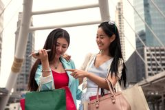 Happy friends shopping in city. Happy friends look at fashion goods in shopping bags. Two beautiful young Asian women enjoying shop in modern city. Black Friday royalty free stock images