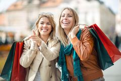 Happy friends shopping. Two beautiful young women enjoying shopping in the city Royalty Free Stock Image