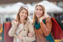 Happy friends shopping. Two beautiful young women enjoying shopping in the city Royalty Free Stock Photo