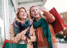 Happy friends shopping. Two beautiful young women enjoying shopping in the city Royalty Free Stock Images