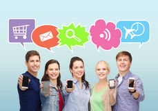 Happy friends showing blank smartphones screens. People, communication, advertisement and technology concept - smiling friends showing blank smartphones screens Royalty Free Stock Images
