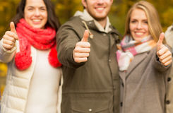 Happy friends showing thumbs up in autumn park Royalty Free Stock Photos