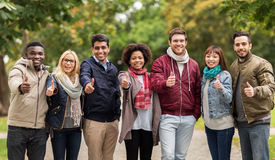 Happy friends showing thumbs up at autumn park Stock Photos