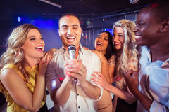 Happy friends singing at the karaoke. In night club Stock Image