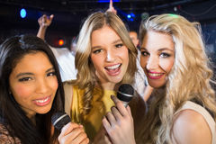 Happy friends singing at the karaoke Stock Images