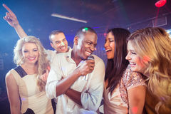 Happy friends singing at the karaoke. In night club Stock Photo