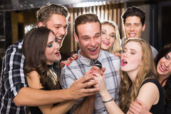 Happy friends singing karaoke together Royalty Free Stock Photos