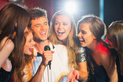 Happy friends singing karaoke together Royalty Free Stock Image