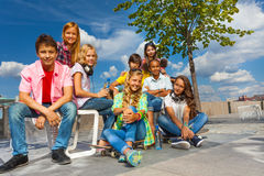 Happy friends sit on chairs of the embankment Stock Images