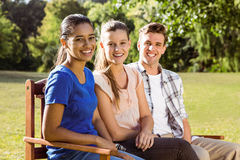 Happy friends sitting on bench. On a sunny day Stock Image