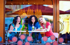 Happy friends sitting on cafe terrace Stock Photos