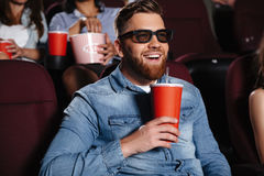 Happy friends sitting in cinema watch film. Picture of happy friends sitting in cinema watch film eating popcorn and drinking aerated sweet water stock photo