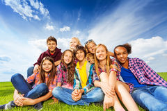 Happy friends sitting on green meadow Royalty Free Stock Photo