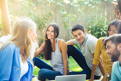 Happy friends sitting with laptop outdoors Royalty Free Stock Image