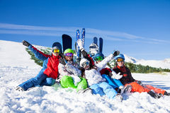 Happy friends sitting with snowboards and skis Stock Images