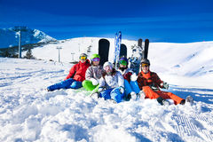 Happy friends sitting with snowboards and skis Stock Photo