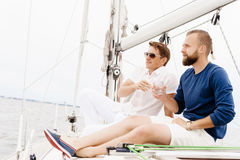 Happy friends sitting together on a deck of a yacht. And drinking an alcoholic drink Stock Photo
