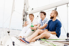 Happy friends sitting together on a deck of a yacht and drinking an alcoholic drink.  Stock Photography