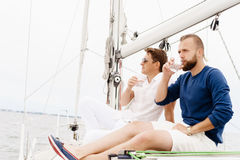 Happy friends sitting together on a deck of a yacht. And drinking an alcoholic drink Royalty Free Stock Image