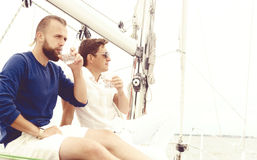 Happy friends sitting together on a deck of a yacht and drinking. Happy friends sitting together on a deck of a yacht enjoying a good day and having a drink Stock Photography