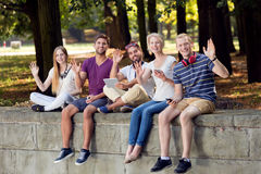 Happy friends sitting together. Happy young friends sitting together on a parapet in the park Royalty Free Stock Images